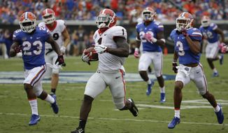 Georgia running back Sony Michel (1) runs past the Florida defense including defensive back Chauncey Gardner Jr. (23), and cornerback Marco Wilson (3) for a touchdown run in the first half of an NCAA college football game, Saturday, Oct. 28, 2017, in Jacksonville, Fla. (AP Photo/John Raoux)