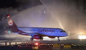 In this Oct. 27, 2017 photo the last plane of German airline Air Berlin is welcomed by the airport fire brigade with a water fountain at Tegel airport in Berlin, Germany. It was the last flight of Air Berlin after the airline declared bankruptcy in August 2017. (Soeren Stache/dpa via AP)