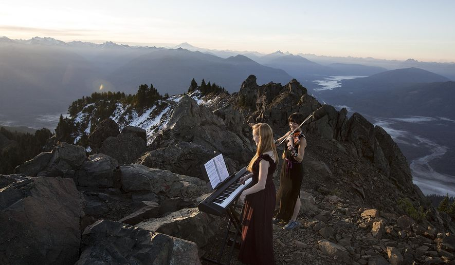 Rose Freeman, center, and Anastasia Allison play atop Sauk Mountain near Concrete, Wash. on Thursday, Oct. 5, 2017. The pair play violin and piano together at sunrise across the Cascades under the name, The Musical Mountaineers. (Ian Terry/The Everett Herald via AP)