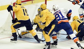 New York Islanders center John Tavares (91) watches a goal by teammate Anders Lee get past Nashville Predators center Calle Jarnkrok (19), of Sweden, and goalie Juuse Saros, of Finland, during the third period of an NHL hockey game, Saturday, Oct. 28, 2017, in Nashville, (AP Photo/Mark Zaleski)