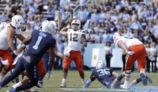 Miami quarterback Malik Rosier (12) passes as North Carolina's Cole Holcomb (36) rushes during the first half of an NCAA college football game in Chapel Hill, N.C., Saturday, Oct. 28, 2017. (AP Photo/Gerry Broome)