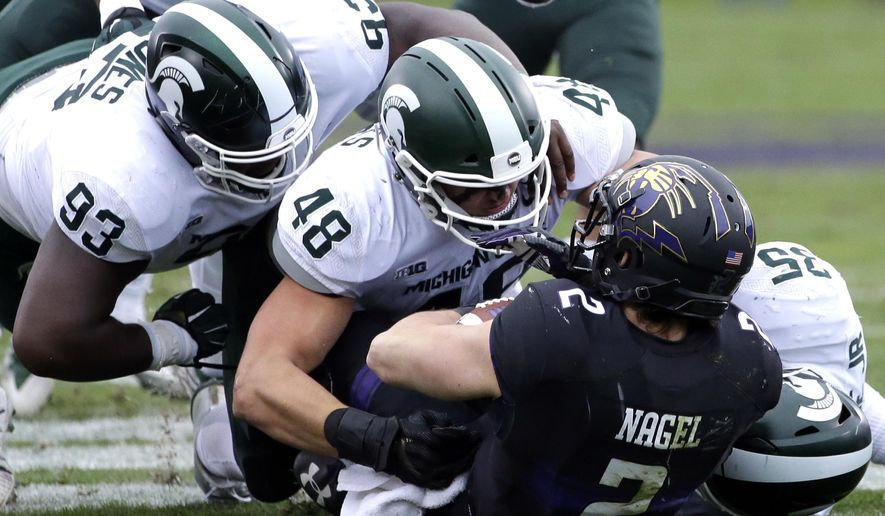 Michigan State defensive tackle Naquan Jones (93), defensive end Kenny Willekes (48) and linebacker Joe Bachie (35) tackle Northwestern wide receiver Flynn Angel (2) during the first half of an NCAA college football game in Evanston, Ill., Saturday, Oct. 28, 2017. (AP Photo/Nam Y. Huh)