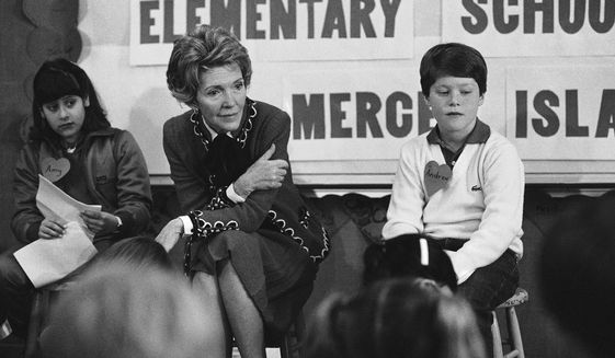 "In this Feb. 14, 1984 file photo, first lady Nancy Reagan sits with a fourth and fifth grade class at Island Park Elementary School on Mercer Island, Wash., where she participated in a drug education class. At left is Amy Clarfeld, 10, and Andrew Cary, 10, is at right. During a visit with schoolchildren in Oakland, Calif., Reagan later recalled, ""A little girl raised her hand and said, 'Mrs. Reagan, what do you do if somebody offers you drugs?' And I said, 'Well, you just say no.' And there it was born."" (AP Photo/Barry Sweet, File)  **FILE**"