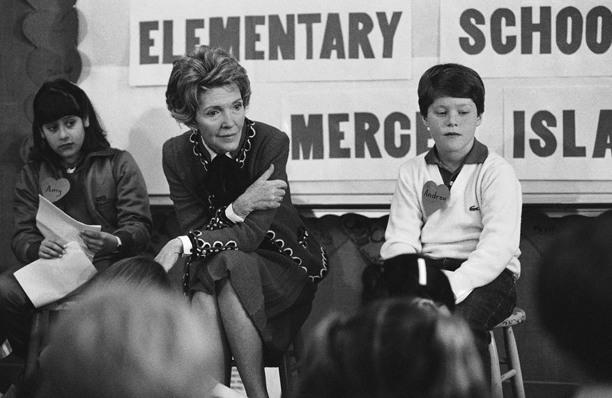 """In this Feb. 14, 1984 file photo, first lady Nancy Reagan sits with a fourth and fifth grade class at Island Park Elementary School on Mercer Island, Wash., where she participated in a drug education class. At left is Amy Clarfeld, 10, and Andrew Cary, 10, is at right. During a visit with schoolchildren in Oakland, Calif., Reagan later recalled, """"A little girl raised her hand and said, 'Mrs. Reagan, what do you do if somebody offers you drugs?' And I said, 'Well, you just say no.' And there it was born."""" (AP Photo/Barry Sweet, File)  **FILE**"""