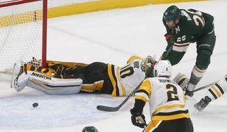 Minnesota Wild's Daniel Winnik, top right, scores against Pittsburgh Penguins goalie Matt Murray, top left, during the first period of an NHL hockey game Saturday, Oct. 28, 2017, in St. Paul, Minn. (AP Photo/Jim Mone)