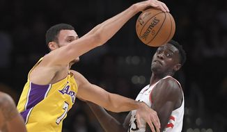 Los Angeles Lakers forward Larry Nance Jr., left, grabs a rebound away from Toronto Raptors forward Pascal Siakam, of Cameroon, during the first half of an NBA basketball game, Friday, Oct. 27, 2017, in Los Angeles. (AP Photo/Mark J. Terrill)