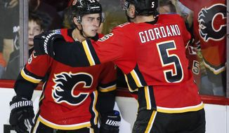 Calgary Flames left wing Johnny Gaudreau (13) celebrates his goal with defenseman Mark Giordano (5) during the second period of an NHL hockey game, Friday, Oct. 27, 2017 in Calgary, Alberta. (Jeff McIntosh/The Canadian Press via AP)