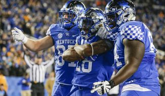Kentucky running back Benny Snell Jr. is congratulated by team mates tight end C.J. Conrad, left, and offensive tackle George Asafo-Adjei during the first half of an NCAA college football game against Tennessee Saturday, Oct. 28, 2017, in Lexington, Ky. (AP Photo/David Stephenson)