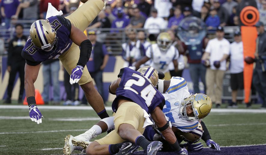 UCLA's Jordan Wilson, right scores against Washington in the first half of an NCAA college football game Saturday, Oct. 28, 2017, in Seattle. (AP Photo/Elaine Thompson)