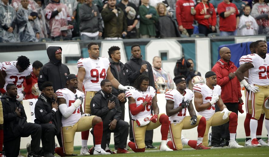Members of the San Francisco 49ers kneel during the national anthem ahead of an NFL football game against the Philadelphia Eagles Sunday, Oct. 29, 2017, in Philadelphia,. (AP Photo/Michael Perez)