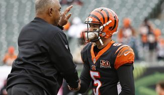 Cincinnati Bengals quarterback AJ McCarron (5) and head coach Marvin Lewis, left, meet on the field during practice before an NFL football game against the Indianapolis Colts, Sunday, Oct. 29, 2017, in Cincinnati. (AP Photo/Frank Victores)