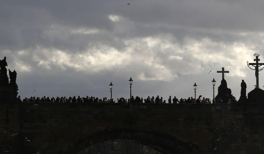 People walk across the medieval Charles Bridge in Prague, Czech Republic, Sunday, Oct. 29, 2017. (AP Photo/Petr David Josek)