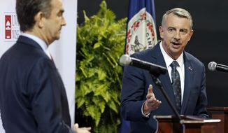 FILE - In this Oct. 9, 2016 file photo Republican gubernatorial candidate, Ed Gillespie, right, gesturing a debate with Democratic challenger Lt. Gov. Ralph Northam at University of Virginia-Wise in Wise, Va. The contest between Gillespie and Northam could be an early referendum on President Donald Trump's political popularity ahead of the 2018 midterm elections. Former Attorney General Eric Holder Jr. and U.S. Sen. Kamala Harris of California spent the weekend of Oct. 28 at get-out-the-vote rallies and black churches trying to rally Democrats around the statewide ticket.  (AP Photo/Steve Helber, File)
