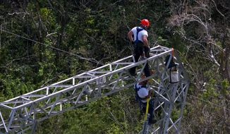 FILE - In this Oct. 15, 2017, file photo, Whitefish Energy Holdings workers restore power lines damaged by Hurricane Maria in Barceloneta, Puerto Rico. The Federal Emergency Management Agency said Oct. 27, it had no involvement in the decision to award a $300 million contract to help restore Puerto Rico's power grid to a tiny Montana company in Interior Secretary Ryan Zinke's hometown. FEMA said in a statement that any language in the controversial contract saying the agency approved of the deal with Whitefish Energy Holdings is inaccurate. (AP Photo/Ramon Espinosa, File)