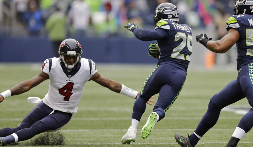 Seattle Seahawks free safety Earl Thomas, second from left, avoids a tackle-attempt by Houston Texans quarterback Deshaun Watson (4) after intercepting a pass from Watson in the first half of an NFL football game, Sunday, Oct. 29, 2017, in Seattle. Thomas returned the interception 78 yards for a touchdown. (AP Photo/Stephen Brashear)