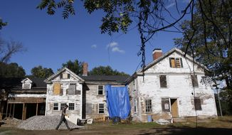 In this Wednesday, Sept. 27, 2017, photo, a worker walks outside the 17th-century homestead where Sarah Clayes lived in Framingham, Mass., after leaving Salem following the 1692 witch trials. After years-long efforts to figure out who owned the home, which had fallen into disrepair after decades of neglect, and to raise enough money to fix it, renovations are expected to be completed by the spring of 2018. (AP Photo/Bill Sikes)