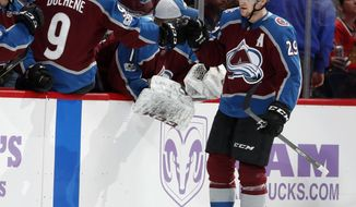 Colorado Avalanche center Matt Duchene, left, reaches out to congratulate center Nathan MacKinnon as he passes the team box after scoring a goal against the Chicago Blackhawks in the second period of an NHL hockey game Saturday, Oct. 28, 2017, in Denver. (AP Photo/David Zalubowski)