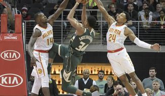 Milwaukee Bucks forward Giannis Antetokounmpo (34) tries to score as Atlanta Hawks center Dewayne Dedmon (14) and forward Kent Bazemore (24) close in on him during the first half of an NBA basketball game, Sunday, Oct. 29, 2017, in Atlanta. (AP Photo/John Amis)