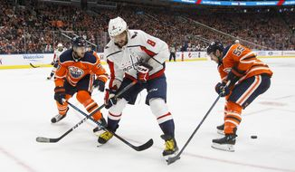 Washington Capitals' Alex Ovechkin (8) battles for the puck with Edmonton Oilers' Oscar Klefbom (77) and Mark Letestu (55) during the first period of an NHL hockey game in Edmonton, Alberta, Saturday, Oct. 28, 2017. (Jason Franson/The Canadian Press via AP)