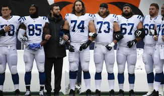 Indianapolis Colts quarterback Andrew Luck, third from left, locks arms with teammates as the national anthem plays before an NFL football game against the Cincinnati Bengals, Sunday, Oct. 29, 2017, in Cincinnati. (AP Photo/Frank Victores)
