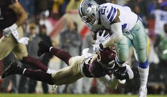 Washington Redskins strong safety Montae Nicholson (35) hangs unto Dallas Cowboys running back Ezekiel Elliott (21) during the second half of an NFL football game in Landover, Md., Sunday, Oct. 29, 2017. (AP Photo/Alex Brandon)