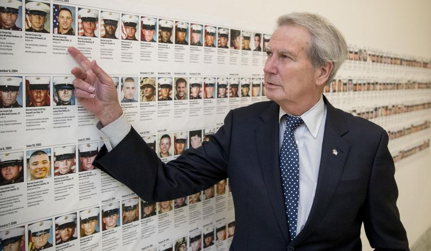 In this Oct. 25, 2017, photo, Rep. Walter Jones, R-N.C. points at a photograph of Marine Sgt. Michael Edward Bits of Ventura, Calif., the first military funeral he and his wife attended, and one of the many pictures of soldiers killed this century based in Camp Lejeune along a hallway leading to his office on Capitol Hill in Washington. As President Trump argued about what he said to the family of a soldier killed in Niger, a North Carolina congressman was quietly doing what he's done more than 11,000 times: signing a condolence letter to that family and others. Republican Rep. Walter Jones began signing the letters to families in 2003 as penance for his 2002 vote supporting war in Iraq. (AP Photo/Andrew Harnik)