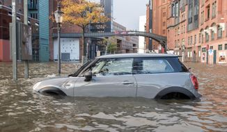 A car stands in the floods near  the Hamburg fish market, early Sunday, Oct. 29, 2017.  High winds struck the country causing flooding and damage in northern and eastern Germany.  (Daniel Bockwoldt/dpa via AP)