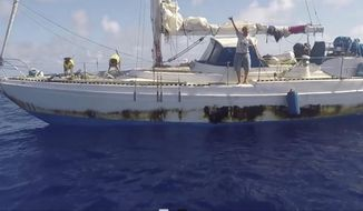 In this Wednesday, Oct. 25, 2017 still image taken from video provided by the U.S. Navy, Jennifer Appel, of Honolulu, holds up a shaka sign as rescuers approach her crippled sailboat, the Sea Nymph, after being lost at sea for months, about 900 miles southeast of Japan. Their engine was crippled, their mast was damaged and things went downhill from there for two women who set out to sail the 2,700 miles from Hawaii to Tahiti. A Taiwanese fishing vessel spotted their boat off Japan and thousands of miles in the wrong direction from Tahiti. The Navy sent the USS Ashland to their rescue. (U.S. Navy via AP)