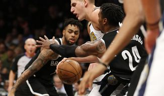 Brooklyn Nets guard D'Angelo Russell, left, and Nets forward Rondae Hollis-Jefferson (24) defend Denver Nuggets center Nikola Jokic, center, during the first half of an NBA basketball game, Sunday, Oct. 29, 2017, in New York. (AP Photo/Kathy Willens)