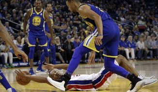 Detroit Pistons' Avery Bradley reaches for a loose ball on the floor beneath Golden State Warriors' Stephen Curry during the first half of an NBA basketball game, Sunday, Oct. 29, 2017, in Oakland, Calif. (AP Photo/Ben Margot)