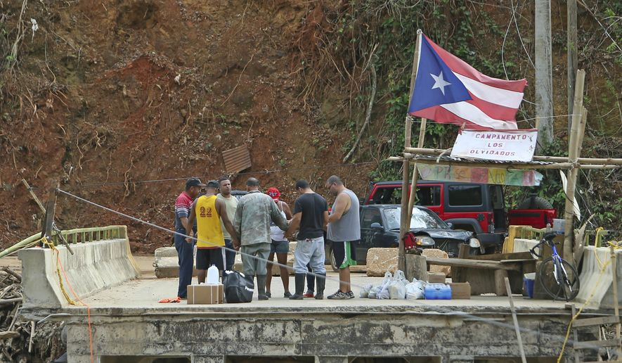 In this Friday, Oct. 27, 2017 photo, good samaritans of the town of Isabela make a circle of prayer with the residents of Rio Abajo in Utuado as recovery efforts from Hurricane Maria continue in Puerto Rico. (David Santiago/Miami Herald via AP)