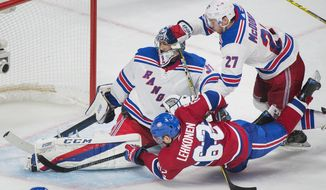 New York Rangers goaltender Ondrej Pavelec, top left, stops a shot from Montreal Canadiens' Artturi Lehkonen (62) as Rangers' Ryan McDonagh defends during third-period NHL hockey game action in Montreal, Saturday, Oct. 28, 2017. (Graham Hughes/The Canadian Press via AP)
