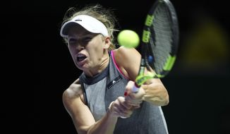 Caroline Wozniacki of Denmark makes a backhand return against Venus Williams of the United States during their singles final match at the WTA tennis tournament in Singapore, on Sunday, Oct. 29, 2017. (AP Photo/Yong Teck Lim)