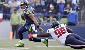 Seattle Seahawks quarterback Russell Wilson, left, scrambles away from Houston Texans' D.J. Reader in the second half of an NFL football game, Sunday, Oct. 29, 2017, in Seattle. The Seahawks won 41-38. (AP Photo/Elaine Thompson)