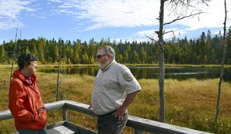 In this Oct. 11, 2017, photo, U.S. Fish and Wildlife Service's Andrew French, right, talks with The Nature Conservancy's Kim Lutz, who also is the chairman of the Friends of the Silvio O. Conte National Fish & Wildlife Refuge, along the Mud Pond Trail in the refuge near Jefferson, N.H. Both support a plan proposed by the U.S. Fish and Wildlife Service that calls for greatly expanding the national refuge which covers parts of the Connecticut River watershed in four New England states. (AP Photo/Michael Casey)