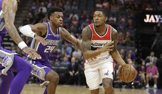 Washington Wizards guard Bradley Beal, right, drives against Sacramento Kings guard Buddy Hield during the first half of an NBA basketball game Sunday, Oct. 29, 2017, in Sacramento, Calif. (AP Photo/Rich Pedroncelli)