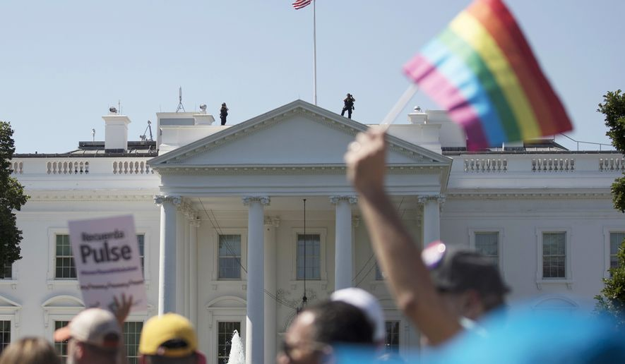 FILE - In this Sunday, June 11, 2017 file photo, Equality March for Unity and Pride participants march past the White House in Washington. A federal court in Washington is barring President Donald Trump from changing the government's policy on military service by transgender people.  (AP Photo/Carolyn Kaster)