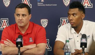 FILE - This Oct. 5, 2017 file photo shows Arizona's Allonzo Trier, right, looking towards head coach Sean Miller as he answers a question during a news conference at McKale Center in Tucson, Ariz. Arizona is expected to be one of the favorites to win the national title, but will play with a cloud hanging over the program after assistant coach Emanuel Richardson was arrested as part of a federal probe into bribes and kickbacks in college basketball recruiting. (Mamta Popat/Arizona Daily Star via AP, file)