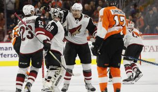 Arizona Coyotes' Luke Schenn, center right, celebrates the win with Scott Wedgewood, center left, and Oliver Ekman-Larsson, of Sweden, left, as Philadelphia Flyers' Wayne Simmonds, right, looks on following the overtime period of an NHL hockey game, Monday, Oct. 30, 2017, in Philadelphia.  (AP Photo/Chris Szagola)