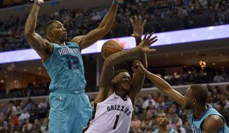Memphis Grizzlies forward Jarell Martin (1) is fouled as he drives between Charlotte Hornets center Dwight Howard (12) and guard Kemba Walker, right, in the second half of an NBA basketball game Monday, Oct. 30, 2017, in Memphis, Tenn. (AP Photo/Brandon Dill)