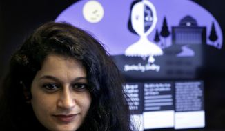 "In this Tuesday, Oct. 24, 2017 photo, co-creator of a fiction-writing 'chatbot,' Massachusetts Institute of Technology postdoctoral associate Pinar Yanardag, of Istanbul, Turkey, sits for a photograph in front of a graphic from the home page of the site called ""Shelley."" Named after ""Frankenstein"" author Mary Shelley, the chatbot has been trained on more than 140,000 horror stories written by amateur writers on a popular online forum. Now Shelley is generating its own stories on Twitter, taking turns with humans in an experiment to find out if artificial intelligence is smart enough to make someone feel scared. (AP Photo/Steven Senne)"