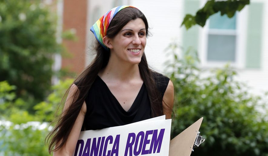 Democratic nominee for the House of Delegates 13th district seat Danica Roem brings campaign signs as she greets voters while canvasing a neighborhood in Manassas, Va. Roem, a former journalist, is challenging longtime incumbent Bob Marshall. If elected, Roem would be the state's first transgender representative. (AP Photo/Steve Helber, File)