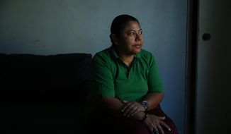 In this Wednesday, Oct. 18, 2017, photo, Iris Acosta, a 51-year-old hotel housekeeper from Honduras, pauses for photos in her sister's apartment in Los Angeles. Acosta is a Temporary Protected Status recipient, a program that is geared toward countries ravaged by natural disasters or war. The program is a temporary fix for immigrants without legal status, designed to avoid the scenario of the government deporting large numbers of immigrants to countries reeling from earthquakes, hurricanes and war. (AP Photo/Jae C. Hong)