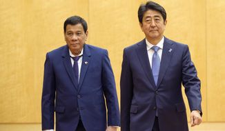 Philippine President Rodrigo Duterte, left, walks with Japanese Prime Minister Shinzo Abe as they review a guard of honor at Abe's official residence in Tokyo Monday, Oct. 30, 2017. Duterte is on a two-day visit to Japan. (Nicolas Datiche/Pool Photo via AP)