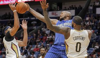 Orlando Magic forward Marreese Speights (5) goes for a rebound between New Orleans Pelicans forward Anthony Davis (23) and forward DeMarcus Cousins (0) in the first half of an NBA basketball game in New Orleans, Monday, Oct. 30, 2017. (AP Photo/Scott Threlkeld)