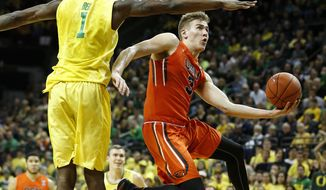 FILE- In this Feb. 20, 2016, file photo, Oregon State's Tres Tinkle, right, jumps toward the basket in front of Oregon's Jordan Bell, left, during the second half of an NCAA college basketball game in Eugene, Ore. Oregon State is looking to finally realize the promise of its 2015 recruiting class that featured Tinkle, Stephen Thompson Jr., and Drew Eubanks with all three players healthy going into this season. (AP Photo/Ryan Kang, file)