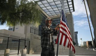 Supporter David Fleeman hangs a flag outside of the federal courthouse, Monday, Oct. 30, 2017, in Las Vegas. Jury selection is set to begin in Las Vegas for the long-awaited trial of Nevada cattleman and states' rights figure Cliven Bundy, two sons and one other co-defendant on charges stemming from an armed standoff with federal agents in April 2014. (AP Photo/John Locher)