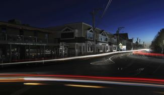 Lights from automobile traffic leave trails on a street in Freeport, Maine, where most outlet shopping stores are closed due to a severe storm knocked out electricity, Monday, Oct. 30, 2017. The severe storm packing hurricane-force wind gusts and soaking rain swept through the Northeast early Monday, knocking out power for nearly 1.5 million homes and businesses and forcing hundreds of schools to close in New England. (AP Photo/Robert F. Bukaty)