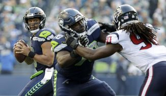 Seattle Seahawks quarterback Russell Wilson, left, drops to pass as Seahawks' Rees Odhiambo, center, blocks Houston Texans outside linebacker Jadeveon Clowney, right, in the second half of an NFL football game, Sunday, Oct. 29, 2017, in Seattle. (AP Photo/Elaine Thompson)