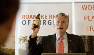 Governor Terry McAuliffe holds up a bottle of Humm Kombucha during an announcement Tuesday, Oct. 31, 2017, that Humm will be building a brewing facility in Roanoke, Va. Humm Kombucha is based in Bend, Or.  (Heather Rousseau/The Roanoke Times via AP) ** FILE **